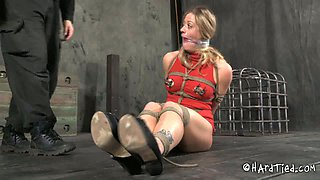 Blonde with clamps on her nipples is lying on the cold floor