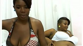 Two sexy ebony sisters play and suck each other's titties on camera