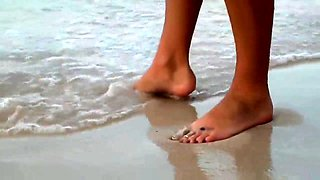 Enticing babe in a sexy bikini gives a footjob on the beach