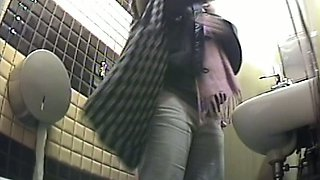 White sexy girl in the public toilet room changes clothes