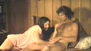 Retro video with a hot brunette giving hand to a man in the bedroom