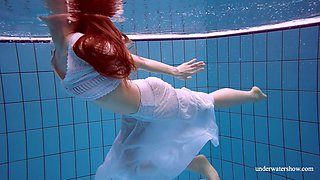 Stunning red haired porn model Marketa shows striptease under the water